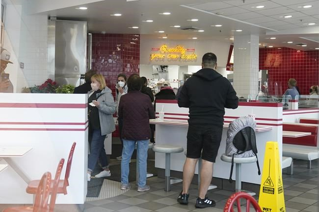 Customers wait for food inside an In-N-Out restaurant in San Francisco's Fisherman's Wharf, Wednesday, Oct. 20, 2021. The In-N-Out hamburger chain is sizzling mad after San Francisco shut down its indoor dining for refusing to check customers' vaccination status. The company's Fisherman's Wharf location, its only one in San Francisco, was temporarily shut by the Department of Public Health on Oct. 14. (AP Photo/Jeff Chiu)