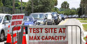 Signage stands at the ready (foreground) in case COVID-19 testing at Barnett Park reaches capacity, as cars wait in line in Orlando, Fla., Thursday, July 29, 2021. The line stretched through the park for more than a mile out to West Colonial Drive near the Central Florida Fairgrounds. Orange County is under a state of emergency as coronavirus infections skyrocket in Central Florida. The Barnett Park site is testing 1,000 people a day and has closed early in recent days due capacity limits. (Joe Burbank/Orlando Sentinel via AP)