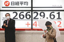 People stand by an electronic stock board of a securities firm showing Japan's Nikkei 225 index in Tokyo, Wednesday, Nov. 25, 2020. Asian shares rose Wednesday after the Dow Jones Industrial Average closed above 30,000 points for the first time despite an ongoing pandemic, as progress in development of coronavirus vaccines kept investors in a buying mood. (AP Photo/Koji Sasahara)