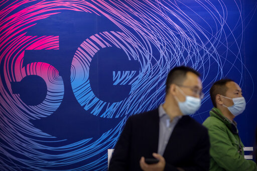 People wearing face masks to protect against the spread of the coronavirus walk past a display advertising 5G wireless services at the PT Expo in Beijing, Wednesday, Oct. 14, 2020. Chinese leaders are shifting focus from the coronavirus back to long-term goals of making China a technology leader at this year's highest-profile political event, the meeting of its ceremonial legislature, amid tension with Washington and Europe over trade, Hong Kong and human rights. (AP Photo/Mark Schiefelbein)