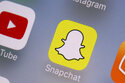 FILE- This Aug. 9, 2017, file photo shows the Youtube, left, and Snapchat apps on a mobile device in New York. The leaders of a Senate panel have called executives from YouTube, TikTok and Snapchat to face questions on what the companies are doing to ensure young users' safety. The hearing Tuesday, Oct. 26, 2021, comes as the panel bears down on hugely popular social media platforms and their impact on children.  (AP Photo/Richard Drew, File)