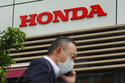 A man wearing a protective mask to help curb the spread of the coronavirus walks past the logo of Honda Motor Company in Tokyo on May 13, 2021. Honda returned to profitability in April-June, recording a 222.5 billion yen ($2 billion) profit, as better sales and costs cuts added to the Japanese automaker's bottom line. (AP Photo/Eugene Hoshiko)