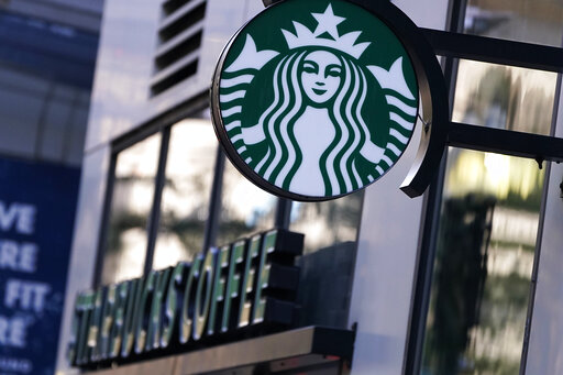 """The """"Siren"""" logo hangs outside a Starbucks Coffee shop, Wednesday, July 14, 2021, in Boston. Starbucks said Wednesday, Oct. 27 it is raising its U.S. employees' pay and making other changes to improve working conditions in its stores.  (AP Photo/Charles Krupa)"""