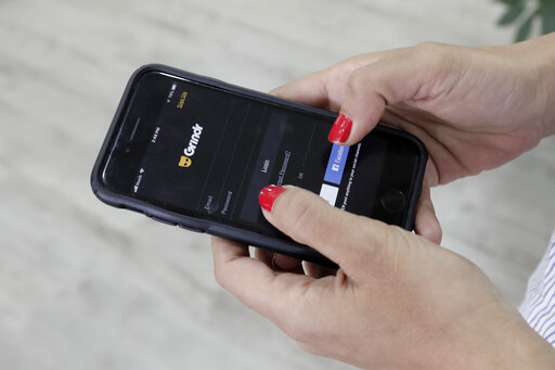 FILE - In this Wednesday, May 29, 2019 file photo, a woman checks the Grindr app on her mobile phone in Beirut, Lebanon. Norway is fining gay dating app Grindr $11.7 million under for failing to get consent from users before sharing their personal information with advertising companies, in breach of stringent European Union privacy rules. Norwegian's data privacy watchdog said Tuesday, Jan. 26, 2021 that it notified the company of its draft decision to issue a fine for 100 million Norwegian krone, equal to 10% of its annual global revenue.  (AP Photo/Hassan Ammar, file)