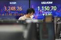 A currency trader watches monitors in front of screens showing Korea Composite Stock Price Index (KOSPI), left, and foreign exchange rate at the foreign exchange dealing room of the KEB Hana Bank headquarters in Seoul, South Korea, Thursday, July 29, 2021. Asian stocks mostly rose Thursday after the Federal Reserve kept its accommodative monetary policies and signaled that economic recovery was on track. (AP Photo/Ahn Young-joon)