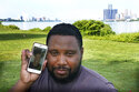 With the cities of Windsor, Ontario, Canada, left, and Detroit, right, seen in the background, Quintin Sweat Jr, poses with his fiancee Renee Harrison, seen on his phone, Tuesday, Aug. 3, 2021, on Belle Isle in Detroit. Sweat and Harrison live only 15 minutes apart by car, with the U.S.-Canada border between them. But the couple, who got engaged in 2019, has only been able to be together three times during the pandemic. (AP Photo/Carlos Osorio)