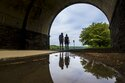 FILE - In this May 14, 2018 file photo, a couple walks on a path at Fairmount Park as they proceed under the trestle bridge over the Schuylkill River in Philadelphia. Tending your garden also offers lessons for growing your money. Start by defining what you want to bring to life. Think about the various aspects of your finances — income, expenses, debts — and imagine what you want them to look like in one or five years' time. (Michael Bryant/The Philadelphia Inquirer via AP)