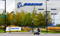 FILE - In this Oct. 28, 2020 file photo, a motorcyclist cruises past the Renton, Wash., Boeing plant where 737's are built. Boeing is temporarily lowering its delivery target for the 787 Dreamliner after discovering additional work that will need to be performed on the aircraft. The company said Tuesday, July 13, 2021, that the 787 production rate will temporarily be lower than five per month and will gradually return to that rate. (Ellen M. Banner/The Seattle Times via AP, File)