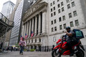 Pedestrians pass the New York Stock Exchange as it operates during normal business hours in the Financial District, Wednesday, Oct. 13, 2021, in the Manhattan borough of New York.  Stocks are off to a mixed start on Wall Street Friday, Oct. 22. The S&P 500, which notched a record high a day earlier, is still on track for its third weekly gain in a row.   (AP Photo/John Minchillo)