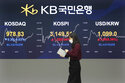 A currency trader passes by monitors showing the Korea Composite Stock Price Inde, and foreign exchange rate at the foreign exchange dealing room of a KB Kookmin Bank branch in Seoul, South Korea, Thursday, Jan. 14, 2021. Shares were mostly higher in Asia on Thursday after a lackluster day on Wall Street, where major indexes spent the day drifting up and down near their record highs. (AP Photo/Ahn Young-joon)