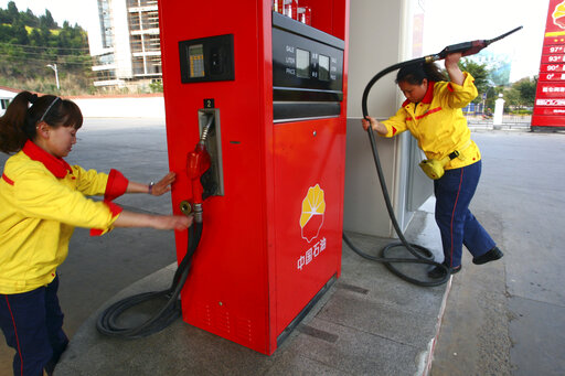 FILE - In this March 26, 2012, file photo, workers operate the pumps at a PetroChina gas station in Suining in southwestern China's Sichuan province. Profit at state-owned companies that dominate China's banking, oil and most other industries rose by as much as 25% in 2020 as the country recovered from the coronavirus pandemic, according to the. State-Owned Assets Supervision and Administration Commission which oversees 97 companies directly under the Cabinet including PetroChina Ltd., Asia's biggest oil producer; China Mobile Ltd., the world's biggest phone carrier by number of subscribers, and Industrial and Commercial Bank of China Ltd., the world's biggest bank by assets. (AP Photo, File)