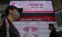 People walk past a bank's electronic board showing the Hong Kong share index at Hong Kong Stock Exchange in Hong Kong Monday, March 8, 2021. Asian shares were mixed Monday, as some indexes were lifted by hopes for a gradual global recovery after the U.S. economic relief package passed the Senate over the weekend. (AP Photo/Vincent Yu)