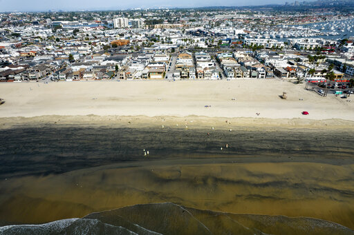 FILE - In this Wednesday, Oct.6, 2021 aerial image taken with a drone, workers in protective suits clean the contaminated beach after an oil spill in Newport Beach, Calif.  California's uneasy relationship with the oil industry is being tested again by the latest spill to foul beaches and kill birds and fish off Orange County. (AP Photo/Ringo H.W. Chiu, File)