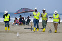FILE - In this Oct. 11, 2021, file photo, a family, background, is under an umbrella as workers continue to clean the contaminated beach in Huntington Beach, Calif. California's uneasy relationship with the oil industry is being tested again by the latest spill to foul beaches and kill birds and fish off Orange County. (AP Photo/Ringo H.W. Chiu, File)