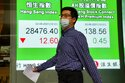 A man wearing a face mask walks past a bank's electronic board showing the Hong Kong share index in Hong Kong, Tuesday, June 22, 2021. Asian shares have rebounded from their retreat a day earlier, tracking Wall Street's recovery from the Federal Reserve's reminder it will eventually provide less support to markets. (AP Photo/Kin Cheung)