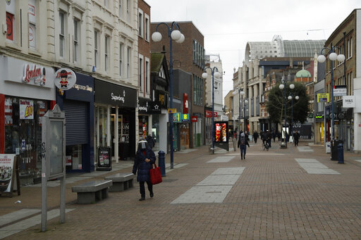 A woman walks wearing a face shield to curb the spread of coronavirus on a quiet shopping street in Kingston upon Thames, south west, London, Tuesday, Jan. 19, 2021, during England's third national lockdown since the coronavirus outbreak began. The U.K. is under an indefinite national lockdown to curb the spread of the new variant, with nonessential shops, gyms and hairdressers closed, most people working from home and schools largely offering remote learning. (AP Photo/Matt Dunham)