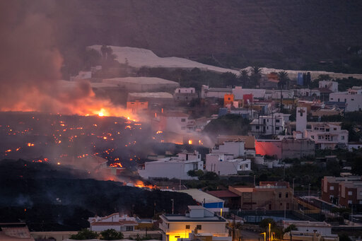 Lava flows from a volcano destroying houses at La Laguna neighbourhood on the Canary island of La Palma, Spain on Thursday Oct. 21, 2021. A second tongue of lava is expected to reach the Atlantic today and release more toxic gases into the atmosphere, an event which will lead to the home confinement of some nearby towns. (AP Photo/Saul Santos)
