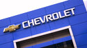 The Chevrolet logo is displayed on the facade of a dealership , Tuesday, Aug. 3, 2021, in Woburn, Mass. Despite a computer chip shortage that temporarily closed some of its factories, General Motors made a healthy $2.8 billion second-quarter net profit in the second quarter.   (AP Photo/Charles Krupa)