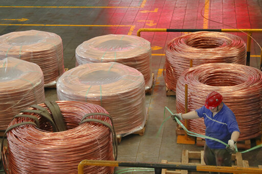 A man works at a factory producing power grid equipment and cable in Nantong city in east China's Jiangsu province Tuesday, July 27, 2021. China's manufacturing growth in July slowed to its lowest level in 15 months as export demand weakened and factories coped with disruptions in supplies of raw materials and components, two surveys found. (Chinatopix via AP)