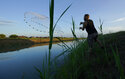 A man casts a net into a canal, Tuesday, Sept. 14, 2021, in McAllen, Texas. Canals used to deliver water in many parts of the Rio Grande Valley lose anywhere from 10% to 40% of the water they carry to seepage and evaporation, according to the Texas Water Development Board, making water a growing concern amid climate change and rising demand that scientists predict will lead to water shortages in the region by 2060.(AP Photo/Eric Gay)