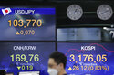 A currency trader walks by the screens showing the Korea Composite Stock Price Index (KOSPI), right, and the foreign exchange rates at the foreign exchange dealing room in Seoul, South Korea, Friday, Jan. 15, 2021. Asian shares were mixed on Friday after a late slide in several Big Tech stocks left major indexes lower on Wall Street. (AP Photo/Lee Jin-man)