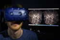 Hadrien Gurnel, software engineer EPFL's Laboratory for Experimental Museology (eM+) explores with a virtual reality helmet the most detailed 3D map of the universe with the virtual reality software VIRUP, Virtual Reality Universe Project developed by Swiss Federal Institute of Technology (EPFL) scientists of the Laboratory of Astrophysics (LASTRO) at EPFL's Laboratory for Experimental Museology (eM+), in St-Sulpice near Lausanne, Switzerland, Tuesday, Oct. 12, 2021. The open-source beta software VIRUP that builds, in real-time, a virtual universe based on the most detailed contemporary astrophysical and cosmological data. (Laurent Gillieron/Keystone via AP)
