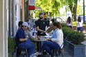 FILE - In this April 16, 2021 file photo, patrons are assisted while dining along a sidewalk in Chapel Hill, N.C.  You and your friends likely have different amounts of money to spend on dinners, movies and other social activities. One friend may think nothing of dropping $50 on a concert ticket, while another may need that cash for bills. So how can friends manage these differences as they reenter the expensive world of socializing?  (AP Photo/Gerry Broome, File)