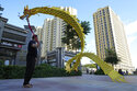 A resident wields a cloth dragon outside the Evergrande Yujing Bay residential complex in Beijing, China, Tuesday, Sept. 21, 2021. Global investors are watching nervously as one of China's biggest real estate developers struggles to avoid defaulting on tens of billions of dollars of debt, fueling fears of possible wider shock waves for the financial system. (AP Photo/Ng Han Guan)