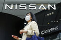 A woman wearing a face mask to to help curb the spread of the coronavirus walks by the logo of Nissan seen at the automaker's showroom in Tokyo Tuesday, May 11, 2021. Nissan reduced its losses for January-March, compared to last year, as restructuring efforts kicked in, despite the sales damage from the coronavirus pandemic, the Japanese automaker said Tuesday.  (AP Photo/Eugene Hoshiko)