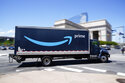 FILE - An Amazon truck drives in in Philadelphia, Friday, April 30, 2021. Amazon wants to hire 125,000 delivery and warehouse workers and said Tuesday, Sept. 14, 2021 that it is paying new hires an average of $18 an hour in a tight job market as more people shop online. The company is also offering pay sign-on bonuses of $3,000 in some parts of the country. (AP Photo/Matt Rourke, file)