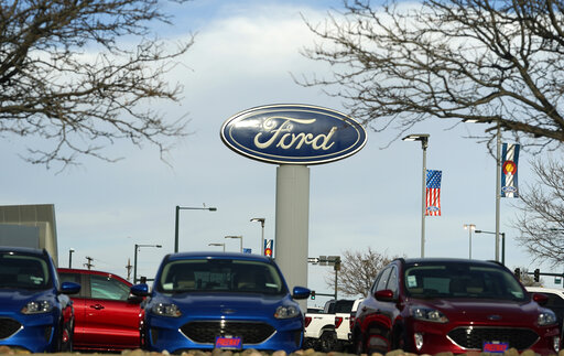 In this Sunday, April 25, 2021, photograph, the blue oval logo of Ford Motor Company is shown over a row of unsold 2021 Escapes at a dealership in east Denver. The global computer chip shortage cut into third-quarter profits at both Ford and crosstown rival General Motors, with both companies having to temporarily close factories, pinching supplies on dealer lots, according to results announced Wednesday, Oct. 27. (AP Photo/David Zalubowski)