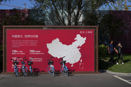 """People walk by a map showing Evergrande development projects in China at an Evergrande new housing development in Beijing on Sept. 22, 2021. China's central bank said Friday, Oct. 15, 2021 that financial risks from China Evergrande Group's debt problems are """"controllable"""" and unlikely to spill over, amid growing investor concerns that the crisis could ripple through other developers. (AP Photo/Andy Wong)"""