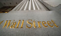 FILE - In this Nov. 5, 2020 file photo, a sign for Wall Street is carved in the side of a building. Stocks are easing lower in early trading on Wall Street, pulling major indexes slightly below the record highs they reached last week. The S&P 500 was down 0.2% in the early going Monday, April 19, 2021, and the Dow Jones Industrial Average fell 0.4%.  (AP Photo/Mark Lennihan, File)