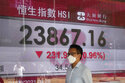 A man walks past a bank's electronic board showing the Hong Kong share index at Hong Kong Stock Exchange in Hong Kong Tuesday, Sept. 21, 2021. Asian shares declined Tuesday, with Tokyo down 2% as worries about heavily indebted Chinese real estate developers weighed on sentiment. (AP Photo/Vincent Yu)