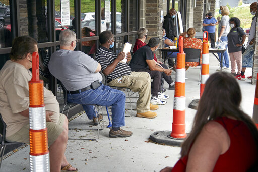 FILE - In this July 15, 2020, file photo, job seekers exercise social distancing as they wait to be called into the Heartland Workforce Solutions office in Omaha, Neb. For the first time in nearly 50 years, older workers are facing higher unemployment than midcareer workers, according to a study released Tuesday, Oct. 20, 2020, from the New School. (AP Photo/Nati Harnik, File)