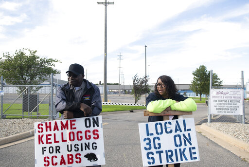 Larry Gamble, who has worked at the Kellogg plant for 13 years, and Sharnita Childress, who has worked at the plant for 8 years, picket with other union workers outside of the plant in Battle Creek, Mich. on Tuesday, Oct. 19, 2021. Around 1,400 union workers from Michigan, Tennessee, Pennsylvania and Nebraska have been on strike for the past two weeks. (Nicole Hester/The Grand Rapids Press via AP)