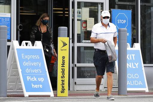 FILE - In this July 30, 2020 file photo, shoppers wear face masks as they leave a Walmart store in Vernon Hills, Ill.  Walmart is reversing its mask policy, Friday, July 30, 2021, and will require vaccinated workers in its distribution centers and stores in areas to wear masks in areas with high infection rates of the virus.  (AP Photo/Nam Y. Huh, File)
