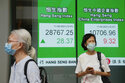 People wearing face masks stand next to a bank's electronic board showing the Hong Kong share index in Hong Kong, Friday, June 11, 2021. Shares were mostly higher in Asia on Friday after the S&P 500 index notched another record high despite a 5% surge in U.S. consumer prices in May. (AP Photo/Kin Cheung)