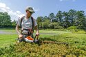 This undated image released by the New York Botanical Garden shows Tyler Campbell using an electric hedgetrimmer to trim hedges at the New York Botanical Garden in the Bronx borough of New York. (Marlon Co/New York Botanical Garden via AP)
