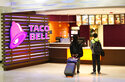 FILE - In this April 19, 2019 file photo, travelers look at a menu at a Taco Bell restaurant inside Miami International Airport in Miami. The company that owns KFC and Taco Bell posted better-than-expected sales in the second quarter thanks to stronger customer demand and a record new store building spree. (AP Photo/Wilfredo Lee, File)