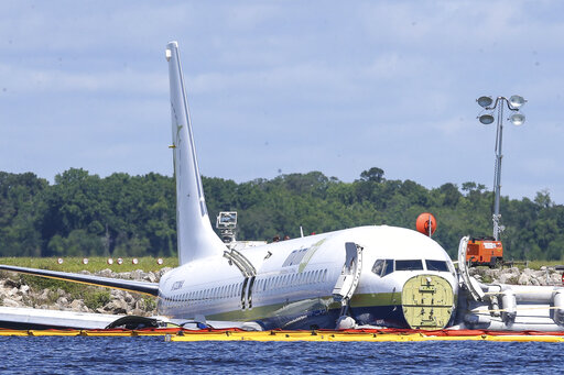 FILE - In this May 4, 2019, file photo, a charter plane carrying 143 people and traveling from Cuba to north Florida sits in a river at the end of a runway in Jacksonville, Fla. Investigators say the loss of braking power on a rain-soaked flooded runway caused a cargo plane chartered by the Pentagon to slide into a Florida river in 2019, the National Transportation Safety Board said Wednesday, AUg. 4, 2021. (AP Photo/Gary McCullough, File)