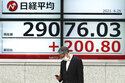 A man wearing a protective mask stands in front of an electronic stock board showing Japan's Nikkei 225 index at a securities firm Friday, June 25, 2021, in Tokyo. Asian shares are rising, buoyed by the rally on Wall Street that came after President Joe Biden announced a bipartisan deal on infrastructure spending. (AP Photo/Eugene Hoshiko)