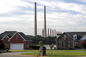 FILE - In this Aug. 7, 2019, file photo, the Kingston Fossil Plant smokestacks rise above the trees behind homes in Kingston, Tenn. The nation's largest public utility is looking at shutting down three of its five remaining coal-fired power plants, saying they are old and no longer practical. At a public hearing this week on the proposed closure of the Kingston Fossil Plant, TVA Senior Manager of Enterprise Planning Jane Elliott stressed the fact that gas provides reliability and flexibility as a fuel that can be called upon at any hour of any day. (AP Photo/Mark Humphrey, File)