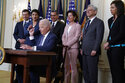 President Joe Biden hands out a pen after signing an executive order aimed at promoting competition in the economy, in the State Dining Room of the White House, Friday, July 9, 2021, in Washington. Standing from left, Transportation Secretary Pete Buttigieg, Lina Khan, Chair of the Federal Trade Commission, Health and Human Services Secretary Xavier Becerra, Commerce Secretary Gina Raimondo, Attorney General Merrick Garland, National Economic Council director Brian Deese, obscured, and Jessica Rosenworcel, Acting Chairwoman of the Federal Communications Commission. (AP Photo/Evan Vucci)