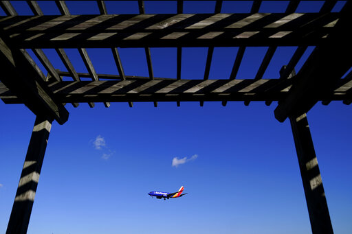 A shelter is seen at the Thomas Dixon Aircraft Observation Area as a Southwest Airlines flight from Jacksonville, Fla., makes its landing approach onto Baltimore-Washington International Thurgood Marshall Airport, Monday, Nov. 23, 2020, in Glen Burnie, Md.  With coronavirus cases spiking in the U.S. and Europe, the financial outlook of the world's airlines is getting worse. The International Air Transport Association said Tuesday that around the world, airlines will lose more than $157 billion this year and next. (AP Photo/Julio Cortez)