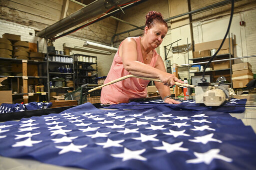 Debbie Wademan, production supervisor, cuts the stars to proper length to make American flags at North American Manufacturing on June 28, 2021 in Scranton, Pa. Since 2016, the staff at North American Manufacturing on Barring Avenue has meticulously produced about 8,000 full-size American flags each year, which are sold to the Defense Logistics Agency and awarded to government retirees. (Jason Farmer/The Times-Tribune via AP)