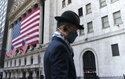 FILE - In this Nov. 16, 2020 file photo a man wearing a mask passes the New York Stock Exchange in New York. Stocks are moving modestly higher in early trading on Wall Street as investors cautiously welcome signs of calm in the bond market. The S&P 500 was up 0.4% early Thursday, March 4, 2021, and the yield on the 10-year Treasury held steady at 1.47%.  (AP Photo/Mark Lennihan, File)