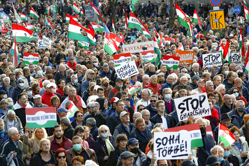 """People hold banners that read """"Never Again"""" during a march marking the 65th anniversary of the 1956 Hungarian revolution, in Budapest, Hungary, Saturday, Oct. 23, 2021. Thousands of supporters of Prime Minister Viktor Orban, who is expected to deliver a speech marking the 65th anniversary of the 1956 Hungarian revolution, march in Budapest, Hungary to demonstrate loyalty to his right-wing government. (AP Photo/Laszlo Balogh)"""