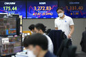 A currency trader passes by screens showing the Korea Composite Stock Price Index (KOSPI), center, and the foreign exchange rate between U.S. dollar and South Korean won, right, at the foreign exchange dealing room of the KEB Hana Bank headquarters in Seoul, South Korea, Friday, June 18, 2021. Asian shares mostly rose Friday, as investors digested the latest message from the U.S. Federal Reserve on raising short-term interest rates by late 2023. (AP Photo/Ahn Young-joon)