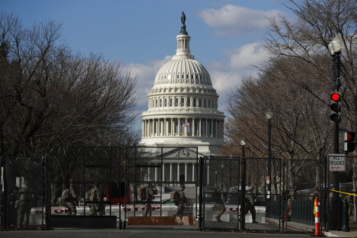 National Guard troops walk outside the Capitol as the security perimeter continues to shrink and many Guard units head home, two days after the inauguration of President Joe Biden on Friday, Jan. 22, 2021 in Washington.(AP Photo/Rebecca Blackwell)